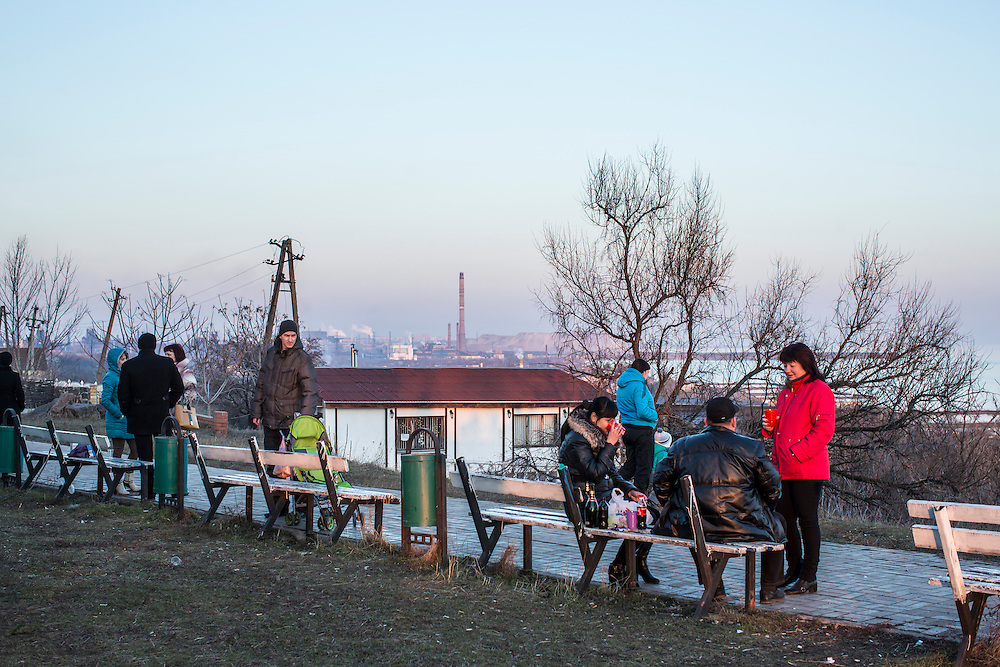 People sit on benches in a park overlooking the Sea of Azov and Azov Steel factory on Sunday, March 8, 2015 in Mariupol, Ukraine. Photo by Brendan Hoffman, Freelance