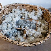 Basket of carded wool with brush. Conner Prairie Interactive History Park provides family-friendly fun for all ages in Fishers, Indiana, USA. Founded by pharmaceutical executive Eli Lilly in the 1930s, Conner Prairie living history museum now recreates life in Indiana in the 1800s on the White River and preserves the William Conner home (listed on the National Register of Historic Places).