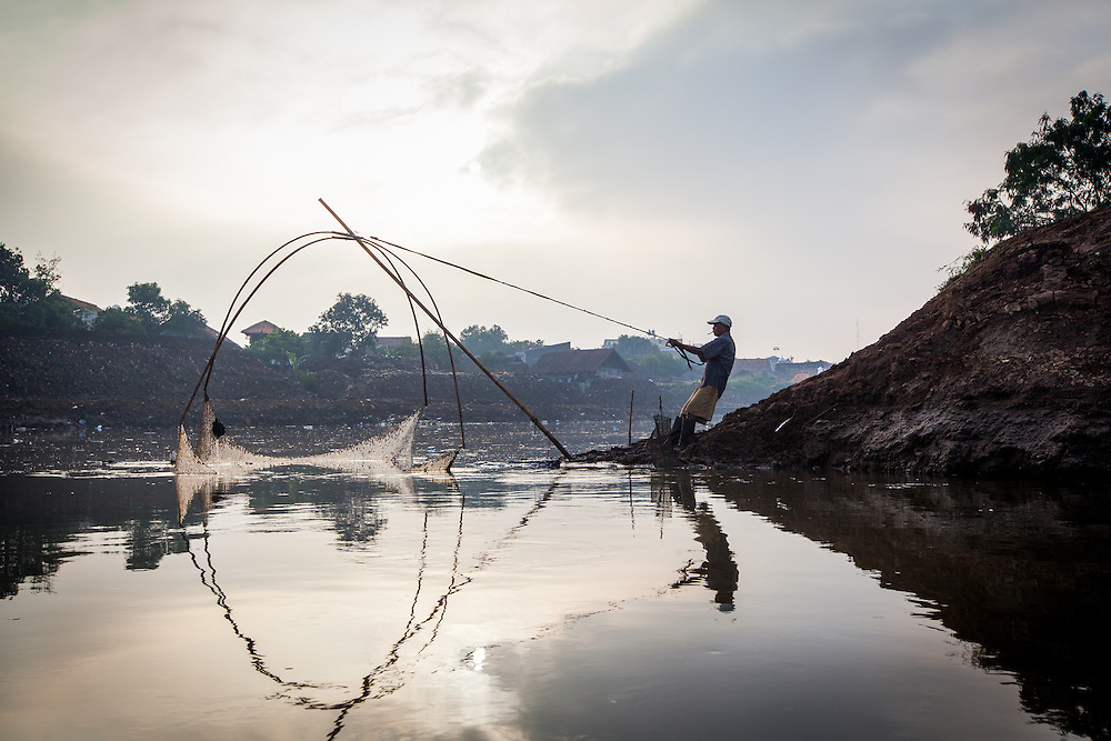 Pak Ade catches fish at the Citarum River. The fish population has significantly declined over the years. Citeureup Village, Kabupaten Bandung...Credit: Andri Tambunan for Greenpeace