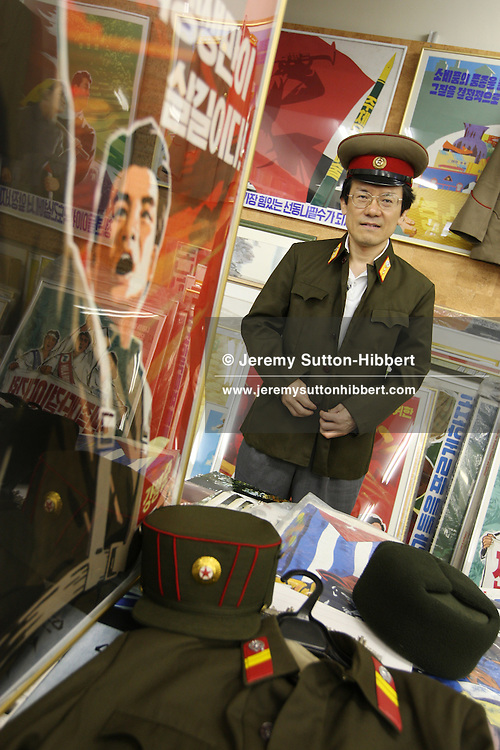 "Mr. Jun Miyagawa, of the Rainbow Trading Company ( a North Korean speciality bookstore) wears a new, and genuine,  North Korean military uniform and hat whilst showing off the North Korean products he has for sale ( including Kim Il Sung badges, North Korean bank notes, football memorabilia, cigarettes, and North Korean propaganda posters and genuine North Korean military uniforms), in his book store in Jimbocho district,  Tokyo, Japan, Friday, Aug. 17, 2007. All the products come via a contact of Mr Miyagawa's in China. The posters are individually painted and range in price from ¥50,000-¥150,000, the Kim Il Sung badges cost approximately JPN Yen 4,000. The products are bought mainly by Japanese 'North Korea fans"", or as Mr. Miyagawa put it ""by Japanese who have a healthy obsession with North Korea""."