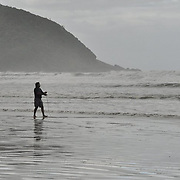 Man fishing at the beach on a cloudy day in Riviera de São Lourenço, Brazil.