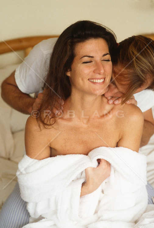 Man kissing woman's neck in bed