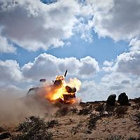 Rebel fighters fire a rocket toward governmet troops on the frontline, near Brega, Libya. March 2011.