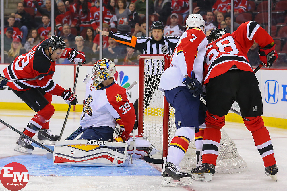 Mar 31, 2014; Newark, NJ, USA; New Jersey Devils center Travis Zajac (19) shoots the puck past Florida Panthers goalie Dan Ellis (39) during the first period at Prudential Center.