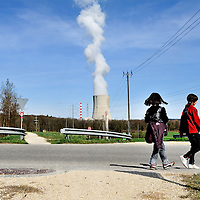 Girls strolling along a road close to G&ouml;sgen Nuclear Power Plant (Kernkraftwerk G&ouml;sgen), with a plume of smoke coming from its cooling tower. <br /> The Swiss are due to vote shortly in a referendum whether to quit nuclear power, which via its five reactors, on four sites, provide almost 40% of the country's power
