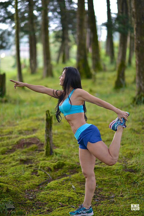 Hispanic brunette woman stretching in a forest.