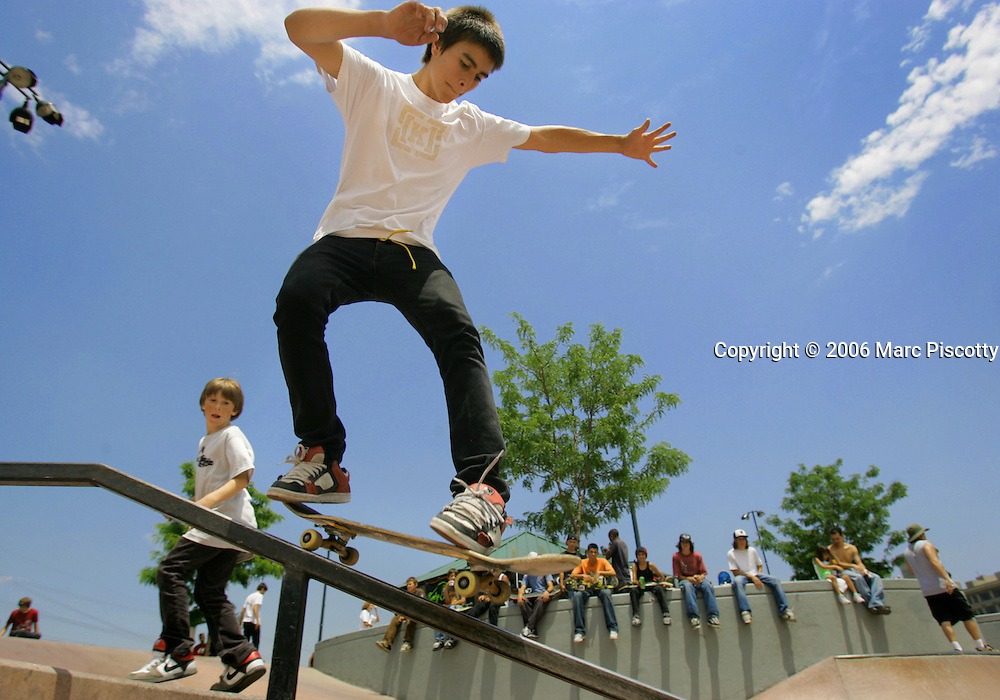 Luke Contreras (center), 16, of Denver ollies onto a rail in the Denver Skatepark as Phil Hansen (left), 9, of Centennial watches on in the background. Denver skateboarders celebrated Go Skateboarding Day Wednesday June 21, 2006 with a rally on the steps of the State Capitol and a convoy of skateboarders down the 16th Street Mall to the Denver Skatepark. The third annual event attracted hundreds of skaters to the park for a day of skateboarding, bands, contests and vendors. It offers skaters an excuse to skip their obligations, go skateboarding for the day and have fun..(MARC PISCOTTY/ © 2006)
