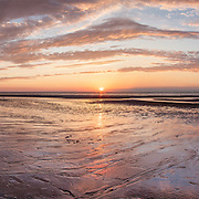 The setting sun lights the tidal flats at Crosby Landing, Brewster.