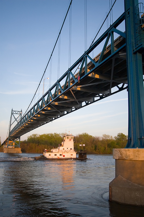 A small towboat ducks under the new US Route 30 bridge over the Mississippi River in Clinton, IA, heading downstream to fetch more barges.