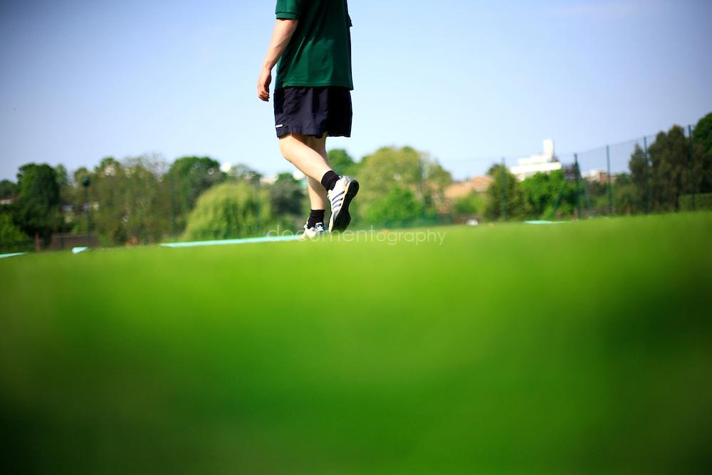 A gardener walks on the grass of Wimbledon