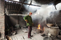 A vietnamese woman works in a foundry of Man Xa, a village in the outskirts of Hanoi considered as one of the most polluted place in Vietnam, Southeast Asia