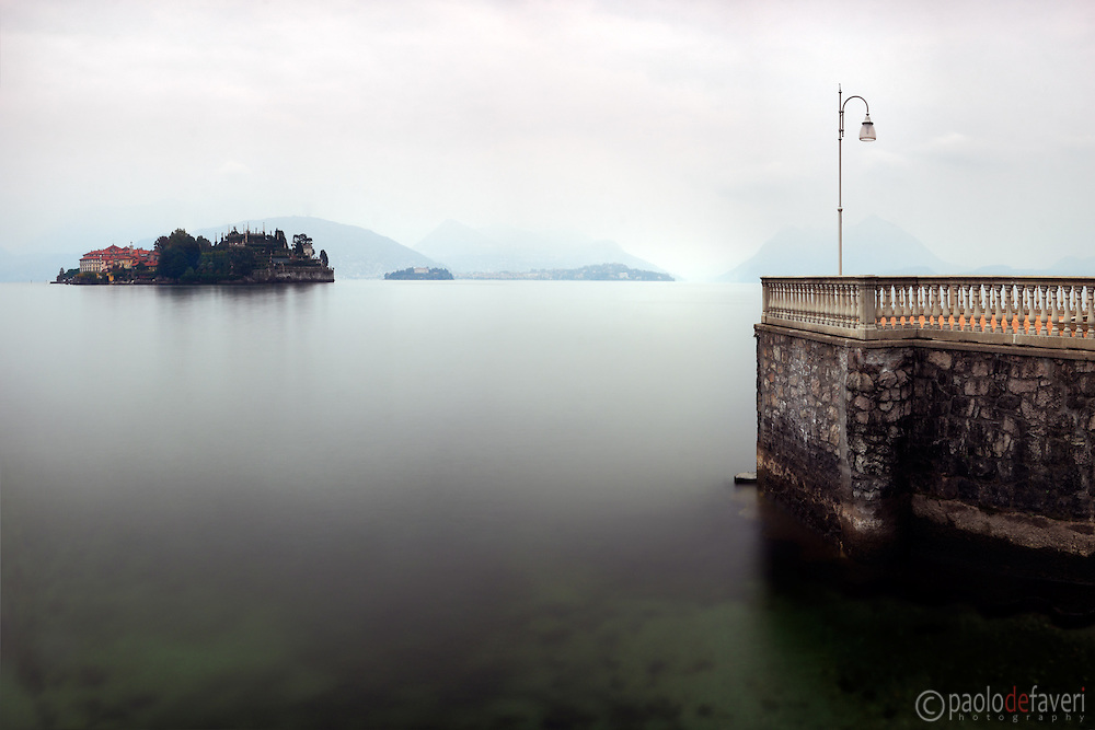 A view from the terrace along the lake Maggiore in Stresa, Piedmont, Italy, on a cold and hazy autumn morning, with Isola Bella in the background.  Stitched from five vertical frames.