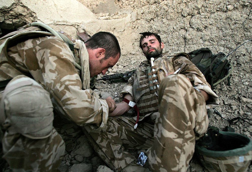 6th July 2007.Kajaki, Helmand Province Afghanistan.Lance Corporal Andrew Howe of 1 Royal Anglian C Coy is given fluids intravenously by a conbat medic as treatment for heat exhaustion in a ruined compound during a firefight with Taliban fighters in Kajaki, Helmand Province, Afghanistan on the 6th July 2007.