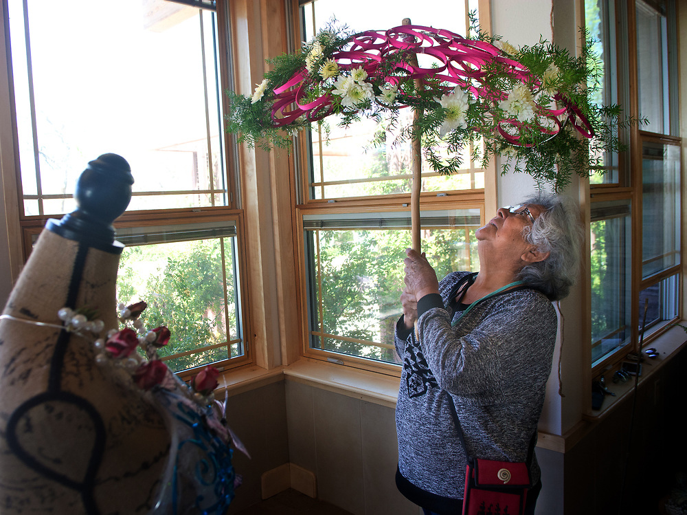 "mkb041617b/metro/Marla Brose --  Cecelia Lucero of Laguna holds a parasol created with flat cane and chrysanthemums as her daughter Shayai Lucero, owner of Earth and Sky Floral Designs, works to install her summer-themed floral display, which includes the parasol, for the second annual Floral Design Show inside the atrium in the High Desert Rose Garden at ABQ BioPark Botanic Garden, Thursday, April 6, 2017, in Albuquerque, N.M. ""She's my support,"" Shayai Lucero said about her mother. ""I glue,"" commented Cecelia about her contributions. The show, which will reflect all four seasons, will continue April 7-9.(Marla Brose/Albuquerque Journal)"