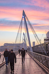 London, January 24th 2017. Photographed from Hungerford Bridge, the early morning light illuminates clouds and buildings of the city's skyline, with the predicted fog failing to appear. High pressure over the UK has caused pollution alerts as fumes are trapped beneath a cold layer of air. PICTURED: Commuters make their way across Hungerford Bridge.