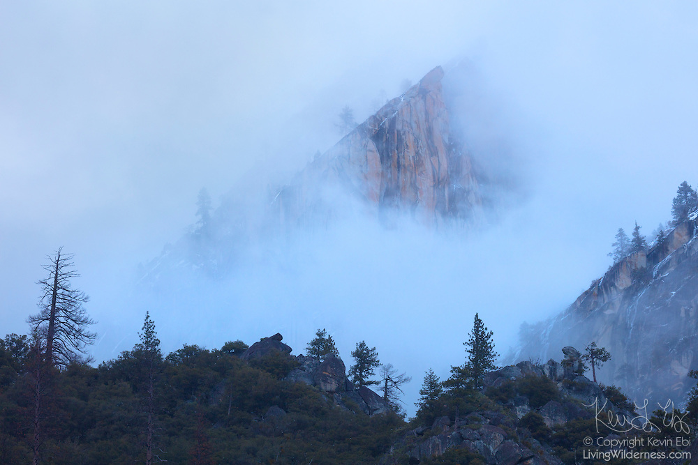 Eagle Peak, a 7,783-foot (2,372-meter) peak that is the highest of the Three Brothers, rises above storm clouds in Yosemite National Park, California.