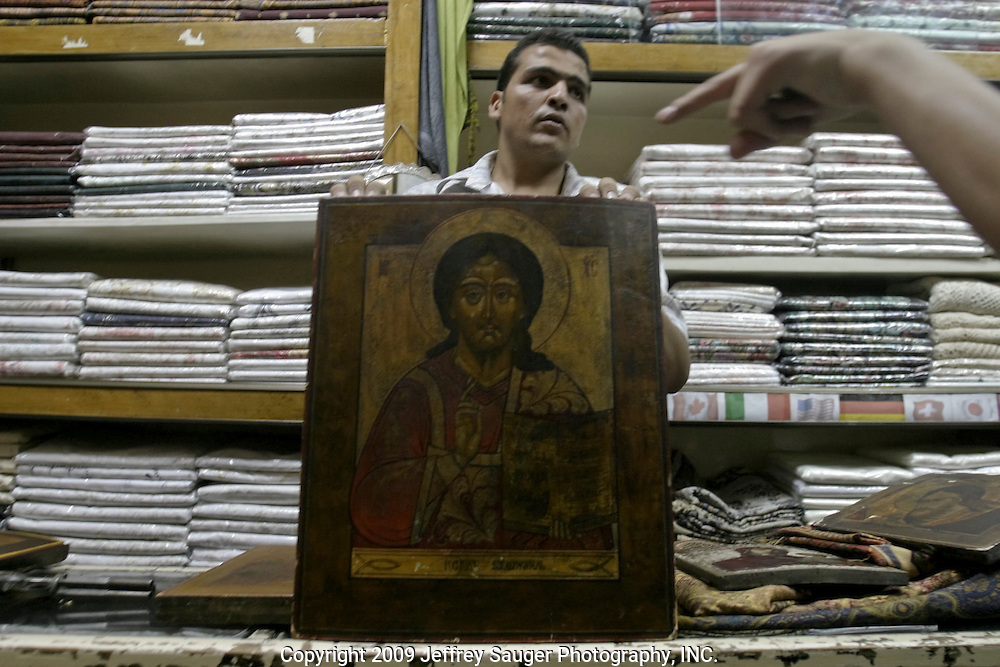 A shopkeeper displays paintings of Jesus, the Virgin Mary and John the Baptist from what he said was the Byzantine era in his clothing and artifacts shop near the Omayyad Mosque in Old Damascus, Syria on July 11, 2003. He started asking $1000 for the smaller Virgin Mary painting and had come down to $600 when the photographer left with just pictures.