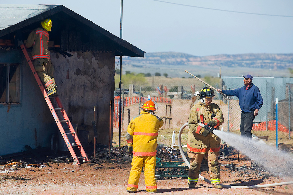 041312       Brian Leddy.Fire officials with Navajo Pine and McKinley County Fire Departments finish extinguishing a blaze at a home in Iyanbito Friday morning. According to officials at the scene, the fire was caused by an electrical malfunction and was mostly outside of the home.