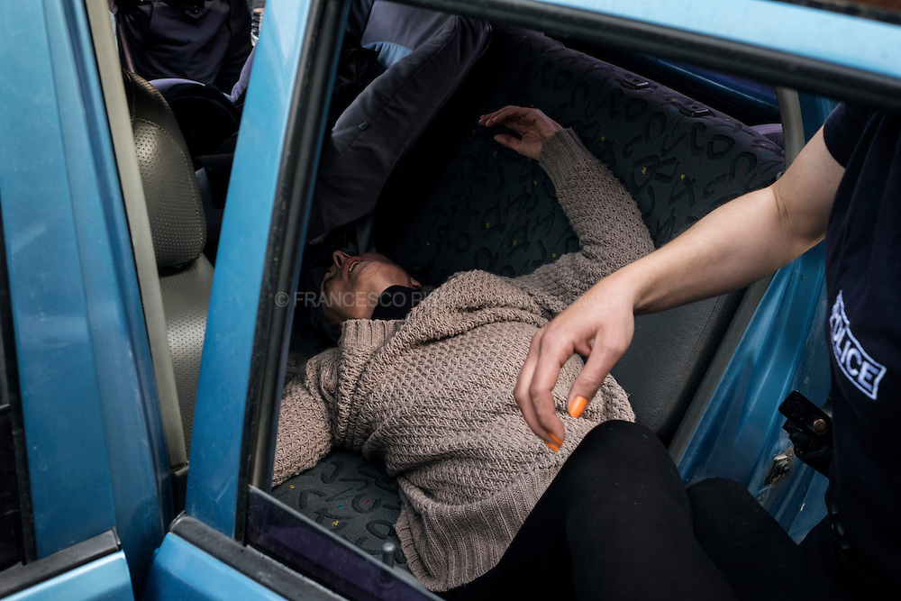 A Syrian woman collapsed during a road block. Migrants block the main road to Macedonia near to Kilikis, northern Greece, Saturday, April 2, 2016. Greece is pressing ahead with plans to start deporting migrants and refugees back to Turkey despite mounting concern from the United Nations and human rights organizations.