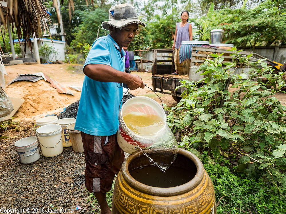 20 JANUARY 2016 - SI LIAM, BURI RAM, THAILAND:  A man fills his home water tanks with water he traveled more than a mile to find in Si Liam, Buri Ram. The man said his rice crop failed this year because of the drought and he didn't know how he was going to get through to the next planting season. The drought gripping Thailand was not broken during the rainy season. Because of the Pacific El Nino weather pattern, the rainy season was lighter than usual and many communities in Thailand, especially in northeastern and central Thailand, are still in drought like conditions. Some communities, like Si Liam, in Buri Ram, are running out of water for domestic consumption and residents are traveling miles every day to get water or they buy to from water trucks that occasionally come to the community. The Thai government has told farmers that can't plant a second rice crop (Thai farmers usually get two rice crops a year from their paddies). The government is also considering diverting water from the Mekong and Salaween Rivers, on Thailand's borders to meet domestic needs but Thailand's downstream neighbors object to that because it could leave them short of water.       PHOTO BY JACK KURTZ