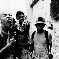 """BEIJING, HAIDIAN DISTRICT, CHINA - AUGUST 15: Tu Qiang (L) and Shen Yue (C) of """"Anarchy Boys"""" and Li Punk hang out together before a punk show August 15, 1999 in the Haidan district of Beijing, China. In the spring of 1998, a handful of youngsters teamed up to unofficially rebel against conformist Chinese life. They shaved their heads, and founded bands with names like """"Brain Failure"""" and """"Anarchy Boys."""" Although the majority of the punks came from well-off families, they preferred to live in self-imposed poverty. The Scream Bar and its surrounding dusty alleyways in the student district became the center of youthful rebellion until it was finally closed in 2000. The punks bands have moved on to other bars in Beijing, some received contracts with foreign record companies and even toured in Europe, Japan and the U.S."""
