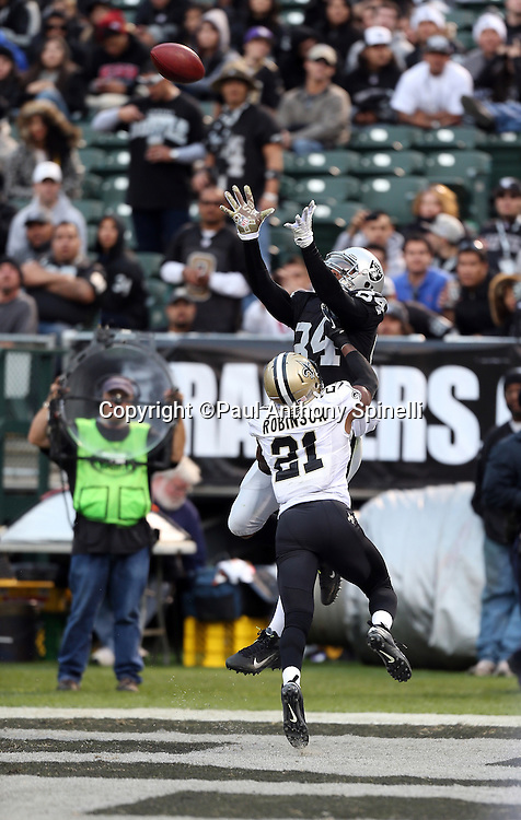 Oakland Raiders wide receiver Juron Criner (84) leaps and reaches for an incomplete end zone pass while covered by New Orleans Saints cornerback Patrick Robinson (21) during the NFL week 11 football game against the New Orleans Saints on Sunday, Nov. 18, 2012 in Oakland, Calif. The Saints won the game 38-17. ©Paul Anthony Spinelli
