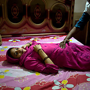 21-year-old Suni is 7 months pregnant and expecting her second baby lays on the bed while her dai (traditional midwife) Afroos checks the position of the baby. <br /> She lives in the Orangi town slum, where only one government hospital provides medical care for around 2.5 million inhabitants. Most women still rely on their community dais to assist their deliveries. <br /> Afroos has been a dai for over 20 years and learned her skills from her blind grandmother. She also works as a dai in the government hospital and did educate her further by following courses provided by the hospital. Orangi town, Karachi, Pakistan, 2010