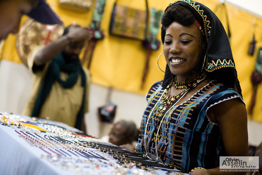 A vendor waits for customers in her booth, offering jewelry for sale, at the 22nd Salon International de l'Artisanat de Ouagadougou (SIAO) in Ouagadougou, Burkina Faso on Friday October 31, 2008.