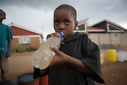 A child drinks contaminated water in the suburb of Budiriro outside of Harare. Others queue to collect clean water in containers brought to collection points where water bowsers have been supplied by NGO's such as UNICEF. ..