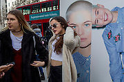 """Models stand next to a street billboard for high-street retailer New Look, outisde London Fashion Week in the Strand, on 17th Febriary 2017, in London, England, United Kingdom. London Fashion Week is a clothing trade show held in London twice each year, in February and September. It is one of the """"Big Four"""" fashion weeks, along with the New York, Milan and Paris. The fashion sector plays a significant role in the UK economy with London Fashion Week alone estimated to rake in £269 million each season. The six-day industry event allows designers to show their collections to buyers, journalists and celebrities and also maintains the city's status as a top fashion capital. (Photo by Richard Baker / In Pictures via Getty Images)"""
