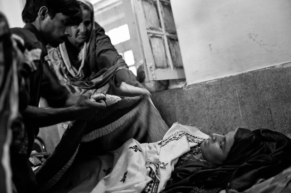 Makhoul and Nazia cover Rabia  with blankets minutes after she had was taken out of the operating theatre after her caesarean section. Thari Mirwah, Pakistan
