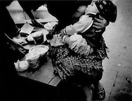 Mother breasts feed child while tending her sidewalk stall in central Guatemala City.