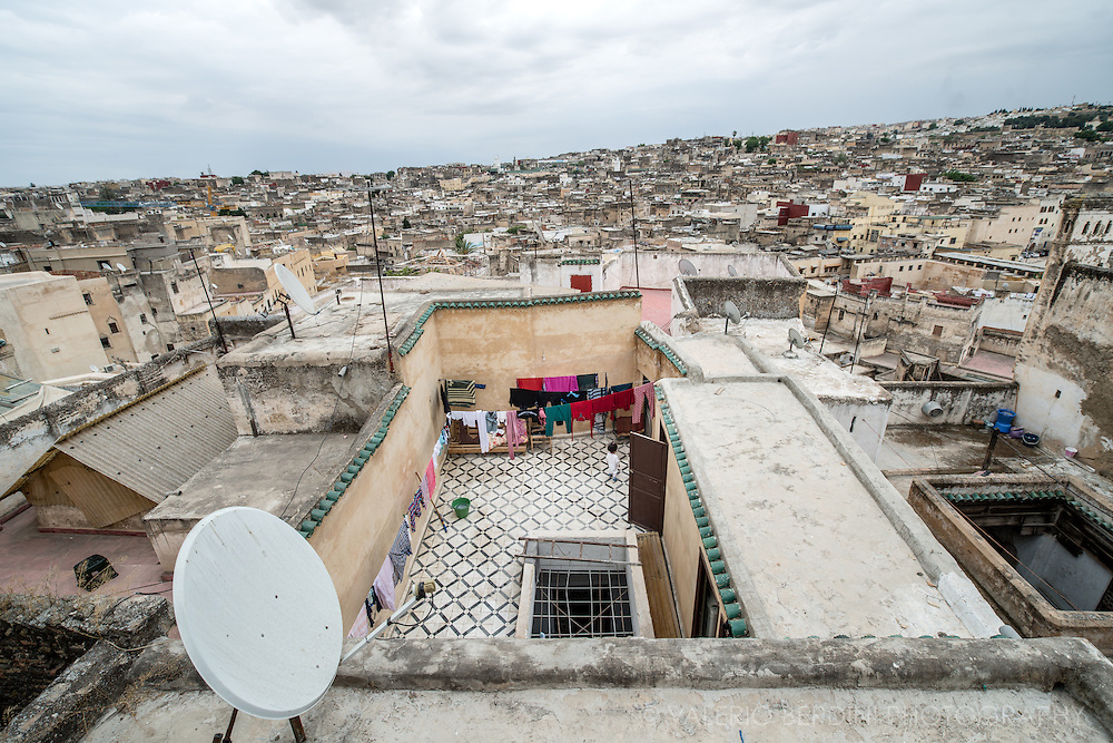 A child plays in a communal terrace overlooking the serpentine Fez medina.