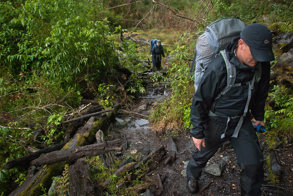 Walkers traverse avalanche debris on the Milford Track, New Zealand, as it passes through the Arthur Valley near Lake Ada