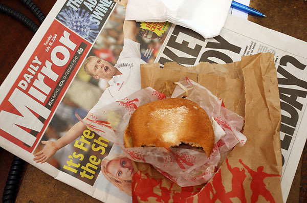 A half-eaten burger on copy of the Daily Mirror newspaper