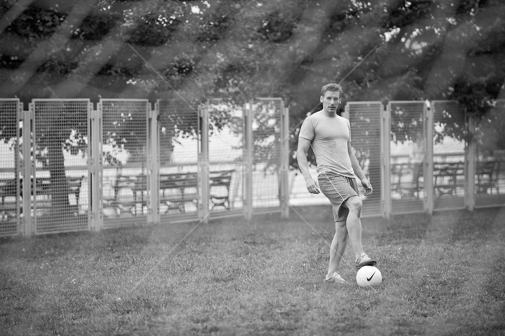 Portraiture of a young man standing with his foot on a soccer ball, (b&w)