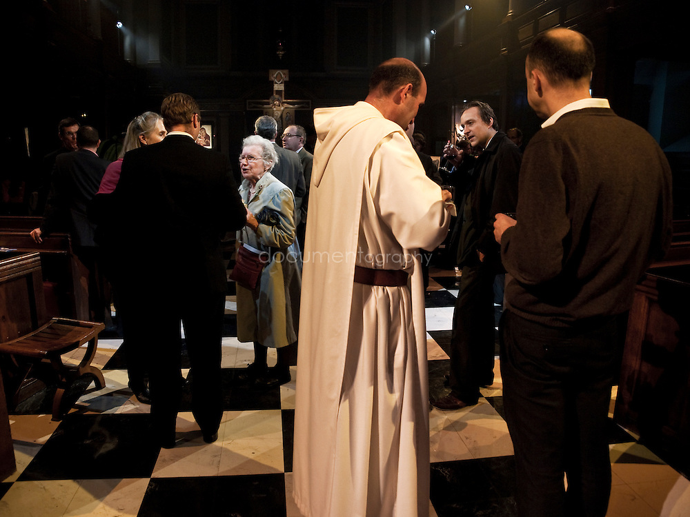 People gather and have food and drinks after the blessing of an icon by the Archbishop of Canterbury, Rowan Williams at St andrews church in Holborn, london.