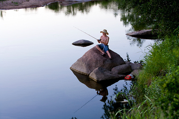 Stock photo of a boy fishing in calm waters from a rock in the Llano River in the Texas Hill Country