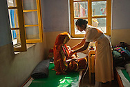 A student nurse cares for a new mother and her baby being cared for at the Kumudini Welfare Trust in Bangladesh. The Trust runs a Nursing school that graduates about 100 students annually.
