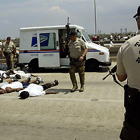 Armed Texas game wardens surround a group of individuals who stole a mail truck to escape the flooded areas of New Orleans East August 31, 2005. The people were freed but forced to continue on foot. Authorities struggled on Wednesday to evacuate thousands of people from hurricane-battered New Orleans as food and water grew scarce and looters raided stores, while U.S. President George W. Bush said it would take years to recover from the devastation. REUTERS/Rick Wilking