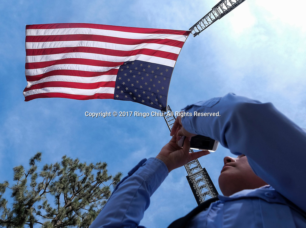 A member of Los Angeles Fire Department takes pictures as a giant U.S. flag flies over the processional route during the funeral of Whittier Police Officer Keith Boyer at Rose Hills Memorial Park in Whittier, Calif., Friday March 3, 2017. Boyer, who was fatally shot after responding to a traffic crash, was remembered today by thousands of law enforcement officers, friends and family as a dedicated public servant, talented drummer, loving friend and even a ``goofy'' dad.(Photo by Ringo Chiu/PHOTOFORMULA.com)<br /> <br /> Usage Notes: This content is intended for editorial use only. For other uses, additional clearances may be required.