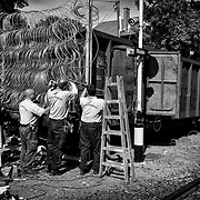 Policemen put barbed wire on a wagon, on september 14, 2015, in order to use it as a gate for the Serbia-Hungary border's fence where refugees used to cross. According to the new hungarian laws, refugees cannot cross the border anymore, excepting in specific control points, otherwise, they will be considered as illegal and will be detained or accompanied back to the border they crossed.
