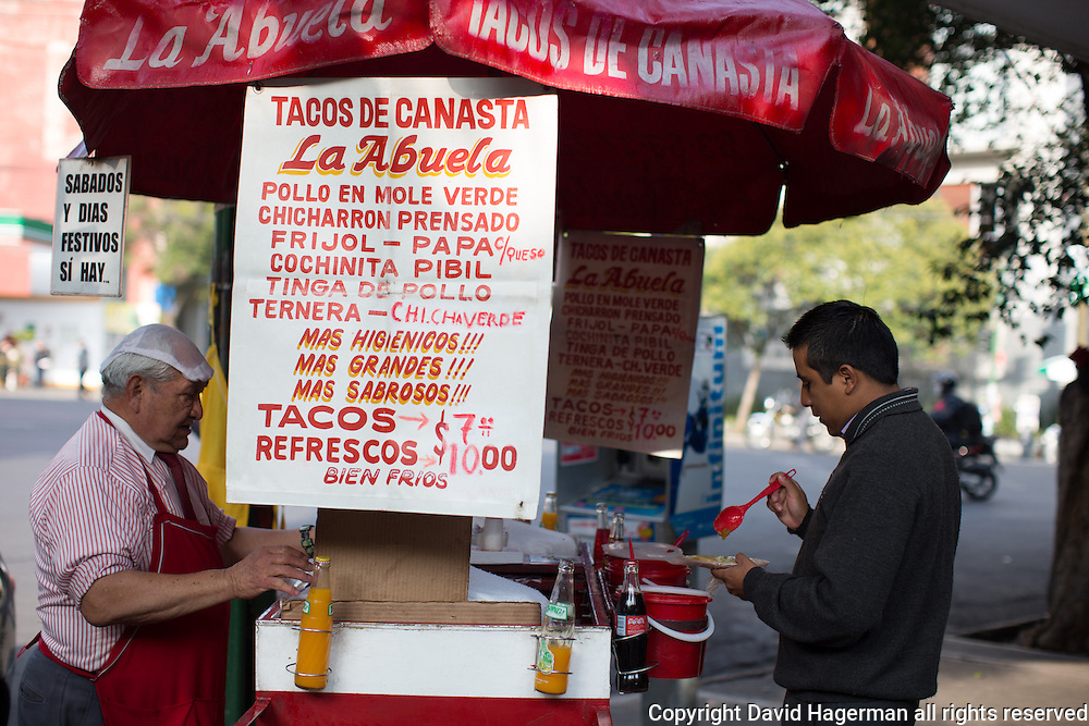 Tacos de Canasta or tacos in a basket are stacked in a basket allowing them to steam. This street cart serves tacos with chicken in green mole, chicharron (fried pork skin) and beans. Tacos canasta are 7 Mexican Pesos a piece (U$.55).