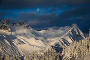 Dramatic image of the moon through the clouds over Mount Fee in the coast mountains of Southwestern BC near Whistler from the Brandywine Bowl snowmobile access road