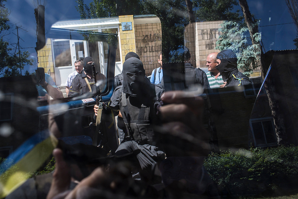 BILOZIRSKE, UKRAINE - MAY 21:  Members of the Donbass Battalion, a pro-Ukraine militia, load in their bus after a meeting with local politicians to ensure the integrity of the upcoming presidential election on May 21, 2014 in Bilozirske, Ukraine. Days before presidential elections are scheduled, questions remain whether the eastern regions of Donetsk and Luhansk are stable enough to administer the vote. (Photo by Brendan Hoffman/Getty Images) *** Local Caption ***