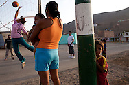 People play volleyball in the street on Saturday, Apr. 18, 2009 in Ventanilla, Peru.