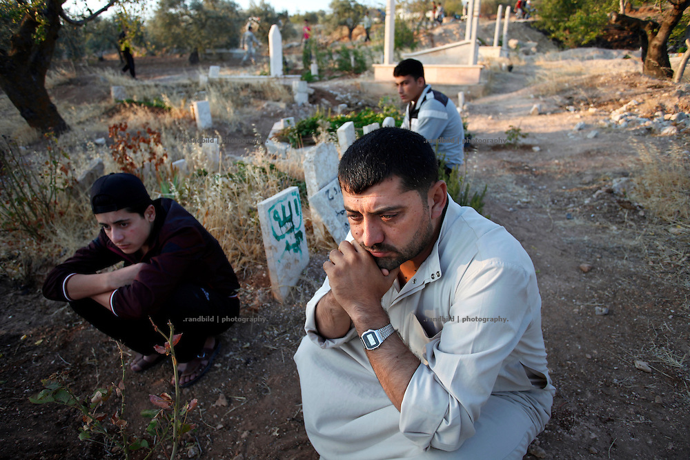 The father of a 10 years old girl who died of her wounds by a missile attack in February 2012 visits her grave in Koreen. During holy Eid al-Fitre (the day following the end of Ramadan) muslims used to visit their relatives graves in the very early morning. Since the Uprising in Syria started cemeteries of the martyrs are more frequented as destiny ties people together.<br /> _ _ _ <br /> Idlib Interim - Challenging life without central government in the village of Koreen (Idlib Province, Syria)<br /> Koreen joint the syrian uprisung to ouster president Bashar al-Assad at a very early stage in 2011. It has been scene of Army attacks and heavy shelling since 2012. In the course of the fightings the village of a few thousend inhabitants was almost abandoned as barrel bomb campaings commited by the regime pounded Koreen. But since regime forces retreated to few bases remaining in Idlib province people returned home to establish a new and almost unregulated economic, social and community life. The regimes power has no affect and can&acute;t reach them anymore. On the other hand a new government isn&acute;t established yet and not in sight at all. Koreen is free to make its way.