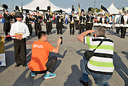 Two men photograph a marching band at the closing ceremonies of the International Children's Games in Windsor, Ontario.