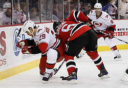 Oct 17, 2009; Newark, NJ, USA; New Jersey Devils defenseman Andy Greene (6) and Carolina Hurricanes right wing Tom Kostopoulos (29) battle for the loose puck during the third period at the Prudential Center. The Devils defeated the Hurricanes 2-0.