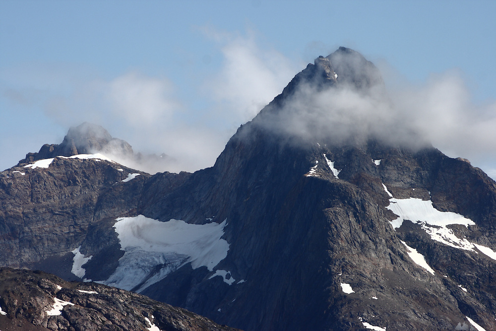 Fog comes over a mountain peak opposite Tasiilaq in south-eastern Greenland